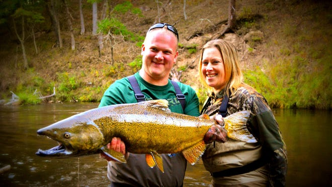 Scott and Charlotte Schnell of White Lake hold a king salmon dog they caught at a Flyin' Heroes veterans' retreat.