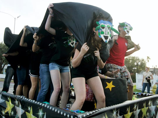 Members of the Campus Activities Board all wear Izzy masks as they stomp and dance on the back of their float on Feb. 7, 2009, during the Texas A&M University-Corpus Christi Homecoming Parade.