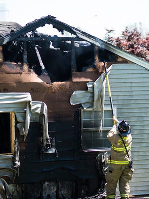 A firefighter pulls away siding to look for hot spots as fire crews battle a two-alarm fire at 1387 Ridge Road in North Lebanon Township on Thursday, June 9, 2016.