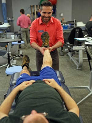 Physical therapist Anthony Carroll works with patient Vinton Bossert in the University of Delaware physical therapy program. The program was recently rated #1 in the country by U.S. News and World Report.