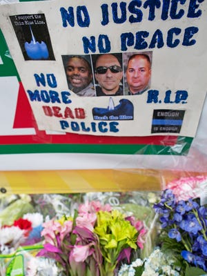 A memorial sign is posted Monday in front of the B-Quick convenience store where law enforcement officers where engaged by a gunman and three were killed on Sunday in Baton Rouge, La.