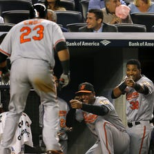 Sep 23, 2014; Bronx, NY, USA; Baltimore Orioles designated hitter Nelson Cruz (23) celebrates a solo home run with Jimmy Paredes (38) and Jonathan Schoop (6) against the New York Yankees during the fifth inning at Yankee Stadium. Mandatory Credit: Adam Hunger-USA TODAY Sports