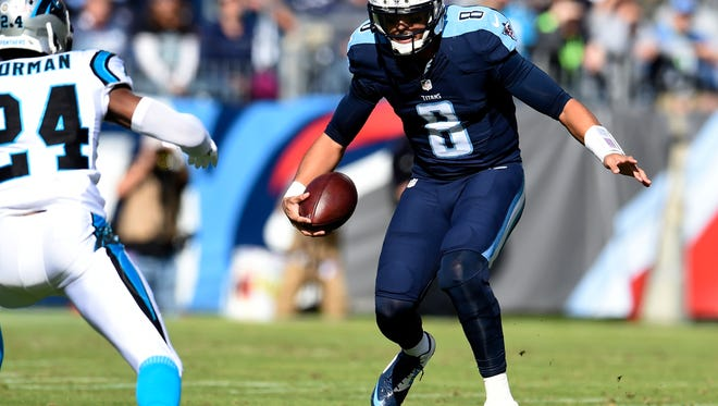 Titans quarterback Marcus Mariota scrambles in the first half against the Panthers, but he would have a much tougher second half.