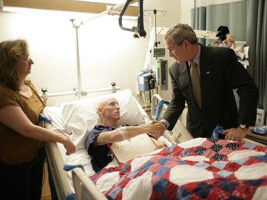 President George W. Bush greets Marine Cpl. Donald Fowler during a visit to National Naval Medical Center in Bethesda, Md.