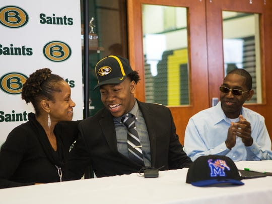 February 7, 2018 - Tanjala Badie, left, hugs her son Tyler after he chooses to play football for University of Missouri during signing day at Briarcrest Christian School on Wednesday. Tanjala's husband and Tyler's father, Shaun, looks on from the right.