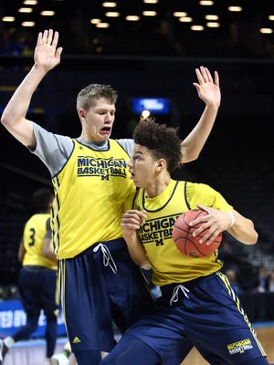 Mar 17, 2016; Brooklyn, NY, USA;  Michigan Wolverines forward D.J. Wilson (right) dribbles against forward Moritz Wagner (left) during a practice day before the first round of the NCAA men's college basketball tournament at Barclays Center.