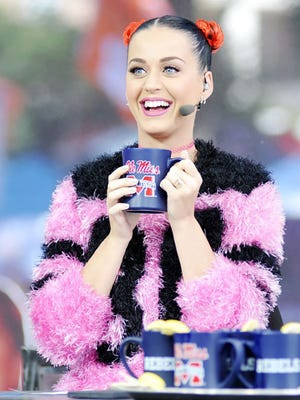 Singer Katy Perry, right, joins host Chris Fowler, left, during telecast of ESPN's College GamDay in The Grove at the University of Mississippi prior to their NCAA college football game in Oxford, Miss., Saturday, Oct. 4, 2014.