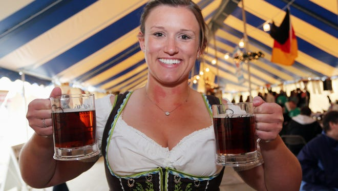 Katrina Patterson of Milwaukee holds a pair of steins of beer during Oktoberfest at Al and Al's Steinhaus on Oct. 3 3, 2015, in Sheboygan.