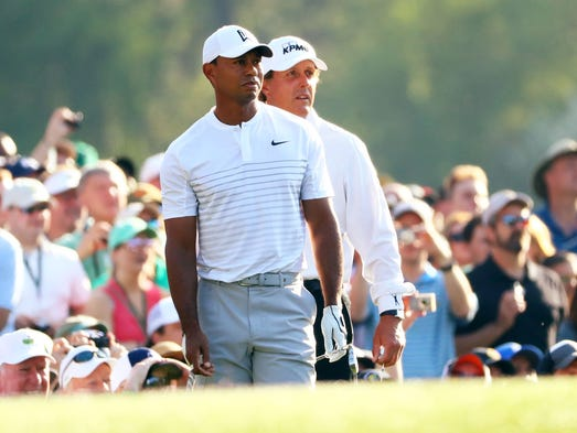 Phil Mickelson watches Tiger Woods play his tee shot
