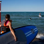 Julie Wiley, of Port Huron, heads out to the water during a stand up paddle board class Wednesday, July 22, 2015 at Lakeside Beach in Port Huron.