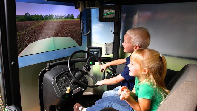 Children experience driving a  tractor in a simulator offered by the South Dakota Corn Growers.