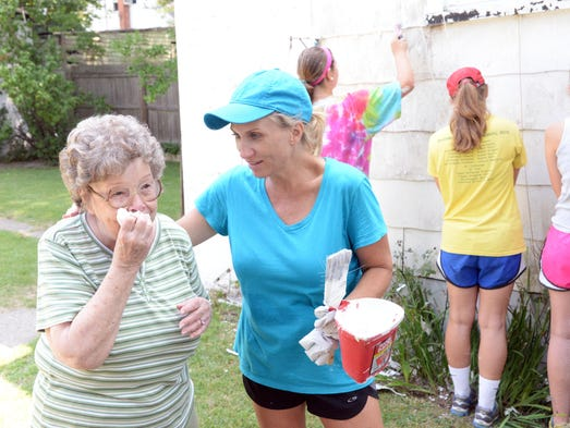Mary Rosypal (left), reacts as Lynn Nayda and other volunteers from Gayton Baptist Church and Toolbox Ministries of Richmond, Va. work on her home at 316 East Vine Street in Millville on Wednesday, July 23, 2014.T  Staff photo/Charles J. Olson