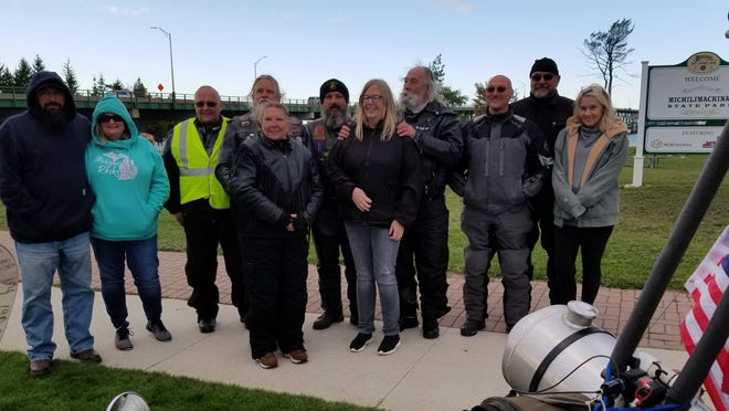 Supporters and fellow riders with Adrian's Phil Comar, fourth from right, assemble Sunday upon reaching the Mackinac Bridge and their destination at Fort Michilimackinac State Park. Comar and several other motorcycle clubs, riders and groups embarked on his annual no-hands ride Sunday morning, which is a fundraiser benefiting research and awareness of Parkinson's disease. The nearly 10-hour trip was completed nonstop with Comar completing the ride no-handed. It is a new world record.