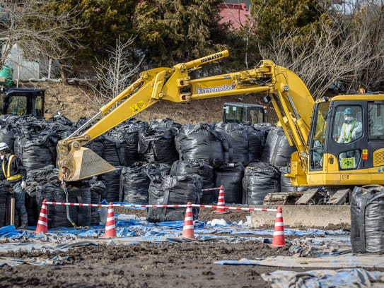 Workers organize large piles of radioactive contaminated