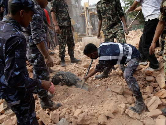 Rescuers search for survivors under the rubble of the