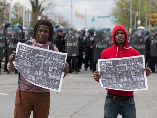 Protesters stand in front of a police line.