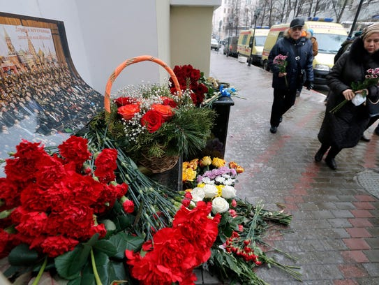 Mourners visit a small memorial outside the home stage
