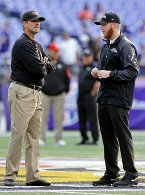 San Francisco 49ers coach Jim Harbaugh, left, chats with his son Jay, a Baltimore Ravens offensive assistant, before a game Aug. 7, 2014, in Baltimore.