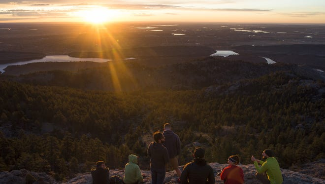 A group views the sunrise on top of Horsetooth Mountain Thursday, April 14, 2016.