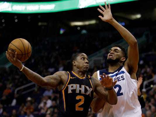 Phoenix Suns guard Isaiah Canaan (2) shoots over Minnesota Timberwolves center Karl-Anthony Towns in the third quarter during an NBA basketball game, Saturday, Dec. 23, 2017, in Phoenix. (AP Photo/Rick Scuteri)
