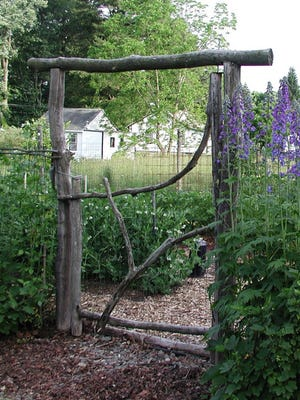 A rustic gate made from locust wood, a rot-resistant wood that will protect and decorate the entrance to this garden for many years to come in New Paltz, N.Y.