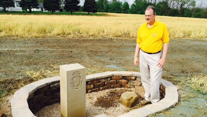 Patrick Simon stands next to the original, crown stone that has worn down over the centuries. Next to it is a replica of what the stone would have looked like originally.