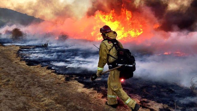 A firefighter battles the Blaine Fire on Sunday, August 13, 2017.