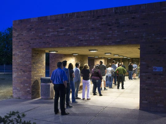 Voters wait in line to vote in Arizona's presidential