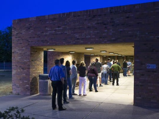 Voters wait in line to vote in Arizona's presidential