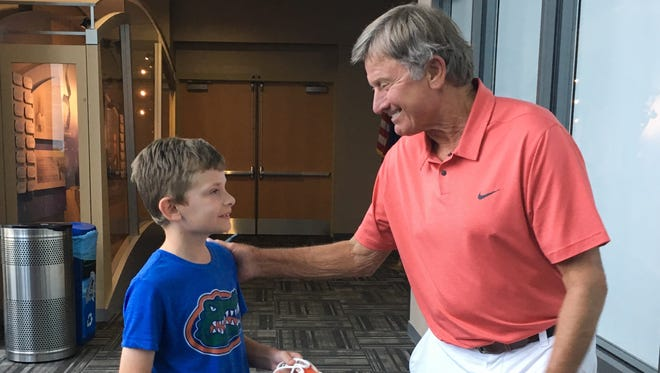 Luke Tuttle, 9, of Suntree, meets Stever Spurrier at Kennedy Space Center Visitor Complex on Tuesday.