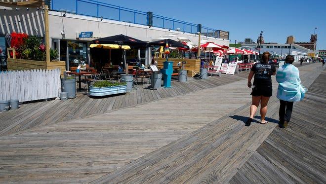 People walk on the Asbury Park boardwalk Thursday past a line of restaurants.