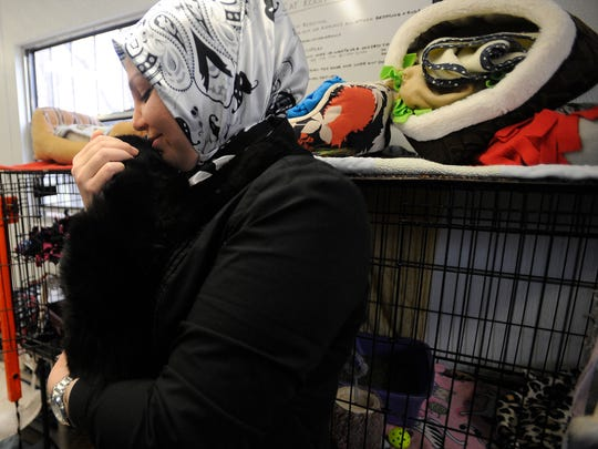 Samah Chamamit of Canton, Mich., holds onto a very shy cat at Almost Home Animal Shelter in Southfield, Mich., on Thursday, Dec. 25, 2014.