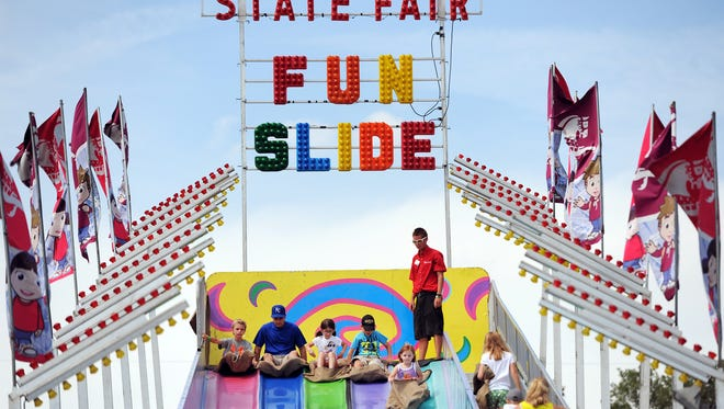 Kids and adults wait to go down the State Fair Fun Slide on the midway during the Indiana State Fair on Saturday, August 17, 2013.