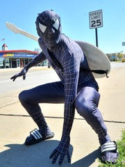 Aaron Vangarde, 27, of Wausau, poses for a photo Monday in a super hero Spiderman costume as part of his job at the Little Caesars Pizza on Stewart Avenue in Wausau.