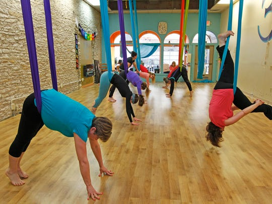 Participants in the  Aerial Yoga Foundation class do the down dog pose at Reaching Treetops Yoga in Waukesha.