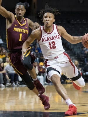 Alabama guard Dazon Ingram (12) drives to the basket against Minnesota guard Dupree McBrayer (1) during the first half of an NCAA college basketball game, Saturday, Nov. 25, 2017, in New York. (AP Photo/Mary Altaffer)