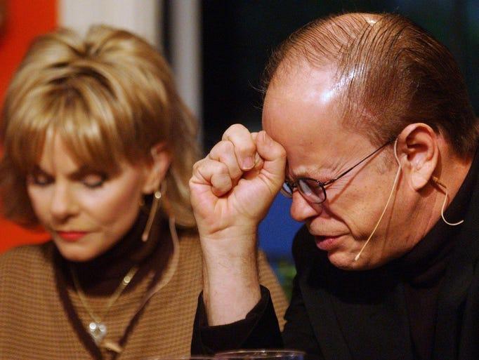 In this 2002 photo, Jim Bakker prays for a member of