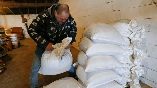 Richard McNulty of Sankey's Feed Mill stacks bags of ground soybeans that are mixed to make livestock feed on Thursday, April 5, 2018, at the facility in Volant, Pa. Rural America is struggling under a cloud of uncertainty as the Trump administration escalates a trade dispute with China. The Republican president says he's simply fighting against unfair business practices with a geopolitical rival. But voters in rural America, those who fueled his 2016 presidential victory, say Trump's moves are threatening their livelihoods and forcing some to re-think their politics.