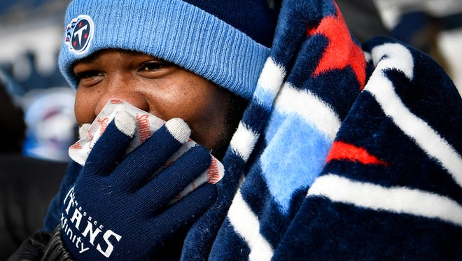 Steven Dalton, of Nashville, warms his face with a hand-warmer before the game between the Titans and the Jaguars at Nissan Stadium in Nashville, Tenn., Sunday, Dec. 31, 2017.