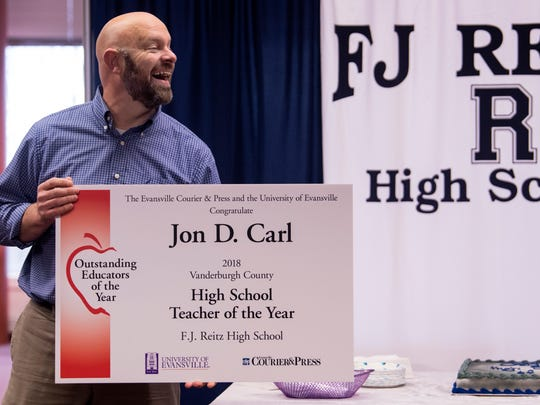 Reitz High School teacher Jon Carl receives the 2018 High School Teacher of the Year award from Dr. Amy McBride (not pictured), a University of Evansville education professor, in the Reitz Media Center, Wednesday, April 4, 2018. The 27th annual awards honor the dedication and contributions of Vanderburgh County K-12 educators at public and nonpublic schools that have at least three years in the profession.