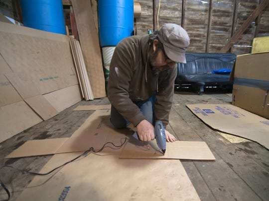 Ben Crane applies hot glue to the cardboard pieces that will eventually become the side supports on the Lego Block Sled