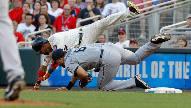 Minnesota Twins'  Eddie Rosario, top, collides with Seattle Mariners first baseman Jesus Montero, bottom, while trying to reach first on a ground ball to second base during the fourth inning of a baseball game in Minneapolis, Saturday, Aug. 1, 2015.