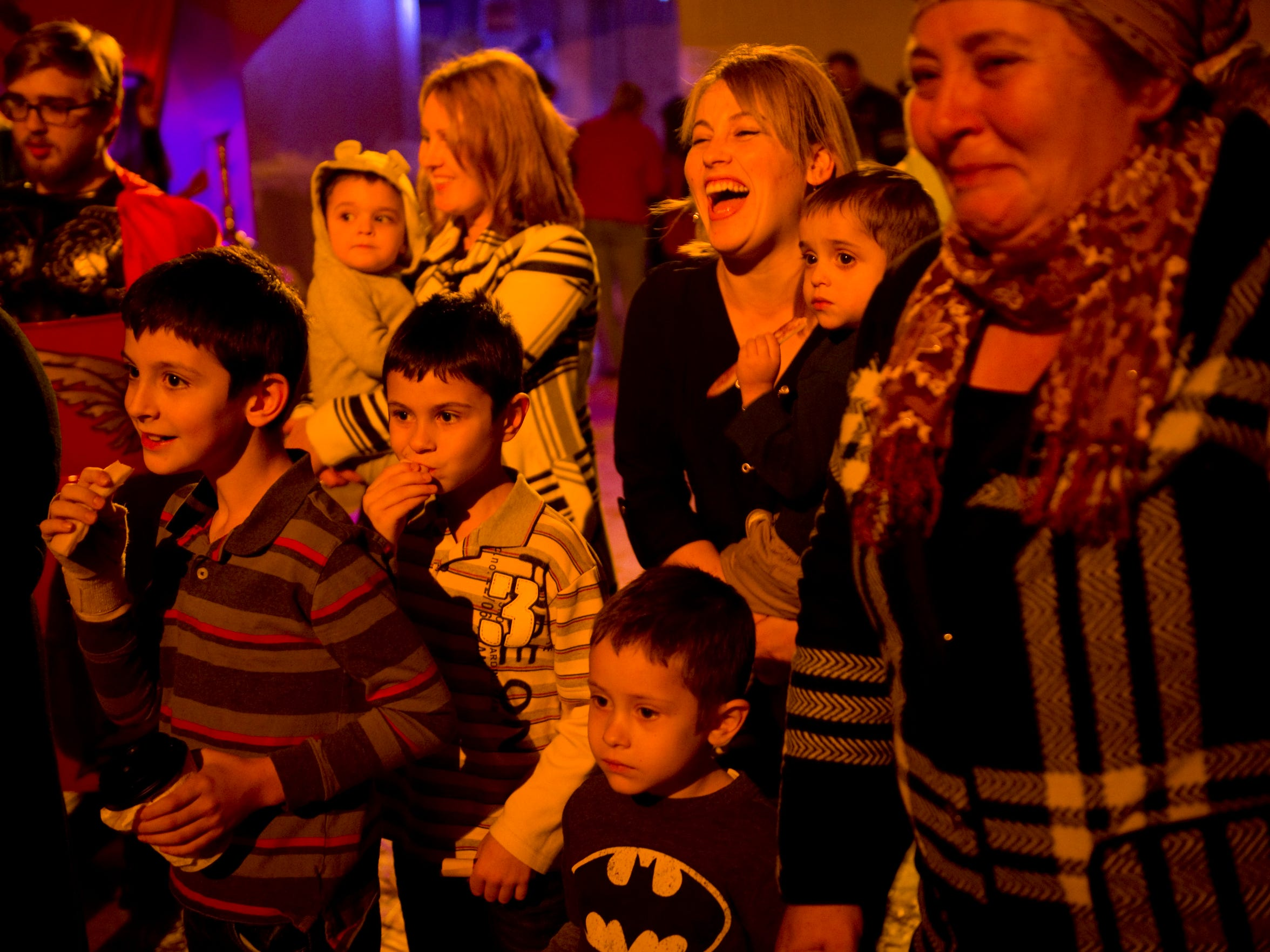 "Inga Malac, second right, and her mother, Maria Ponomarenco, right, find humor in the scene playing out in front of them as they tour old Bethlehem during Grace of Christ Slavic Baptist Church's ""Back to Bethlehem"" program last Saturday night. A thief was being punished and placed in the stocks when his beard fell off."