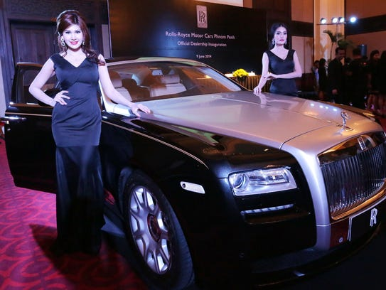 Cambodian models stand next to a Rolls Royce Ghost