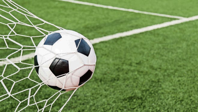 Image of Soccer football in Goal net with green grass field. For sport concept.