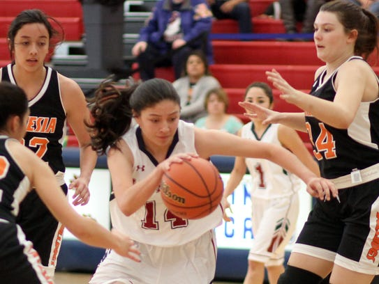Lady Cat Adriana Giron (14) splits the Artesia defense