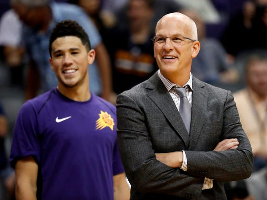Phoenix Suns head coach Jay Triano and guard Devin Booker smile during the second half of an NBA basketball game against the Utah Jazz, Wednesday, Oct. 25, 2017, in Phoenix. (AP Photo/Matt York)