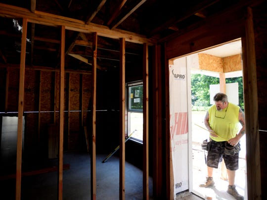 Michael Neely works on a Fuller home which will go