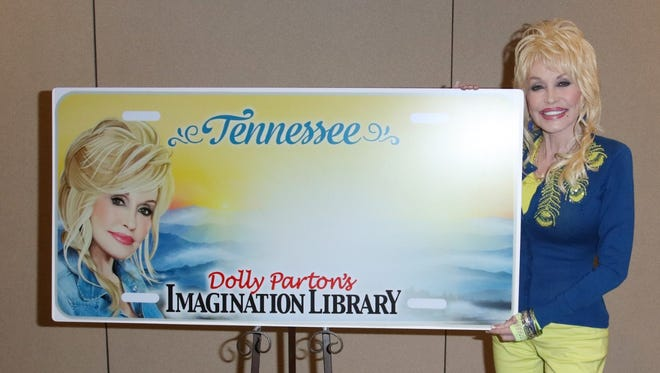 Dolly Parton poses with the new Tennessee license plate, which features the Imagination Library logo, her likeness and a silhouette of the Great Smoky Mountains.