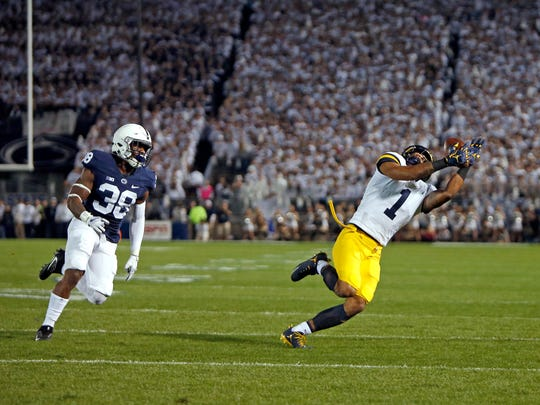 Michigan's Kekoa Crawford catches a pass against Penn State's Lamont Wade, Oct. 21, 2017 at Beaver Stadium in University Park, Pa.